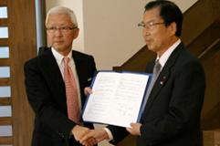 城陽市との調印式で奥田敏晴市長(右)と磯彰格理事長(左)